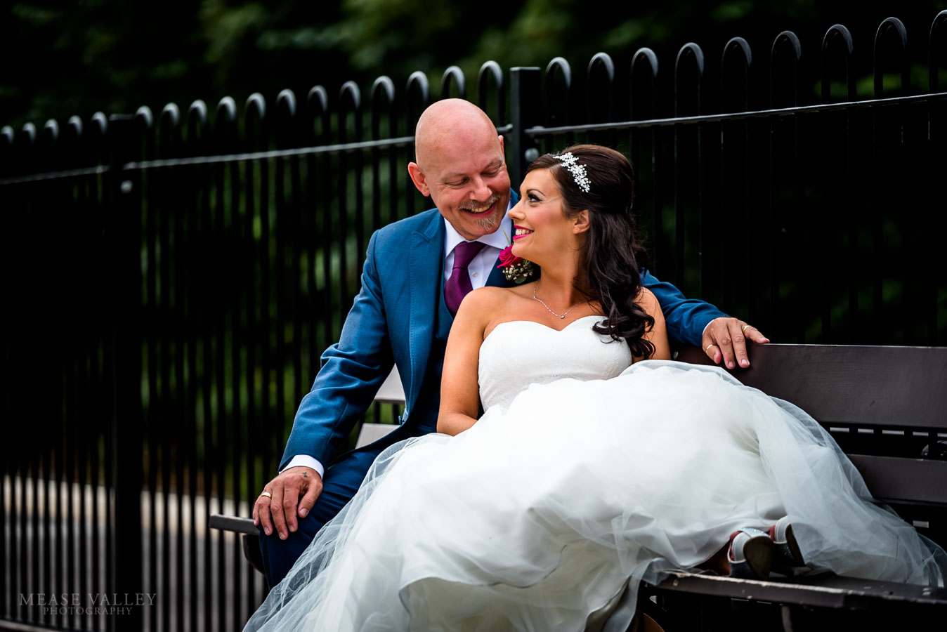Photograph of bride and groom sitting on a bench in Solihull